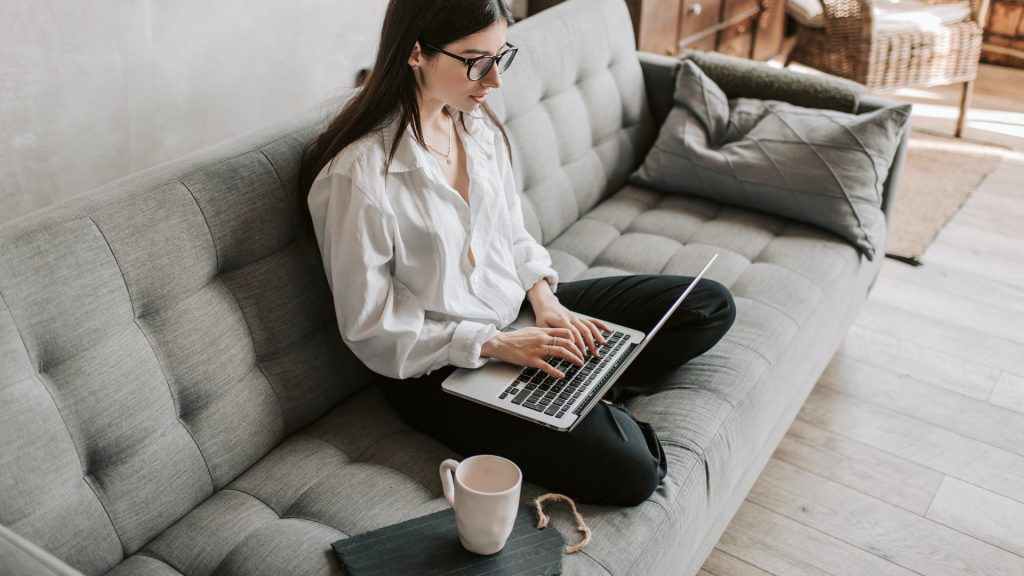 A young woman sitting on the gray couch and working on laptop